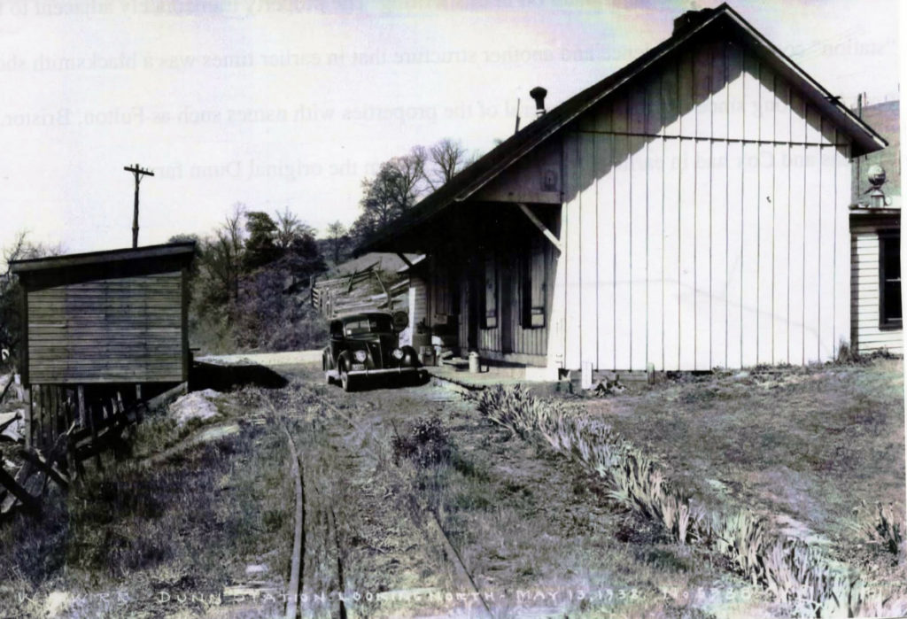 "This picture circa 1938 of the ""station"" at Dunnas Station the location of my childhood and formative years.  The building housed the station of a narrow gauge railroad, a post office and a general store.  On the left is a small warehouse."